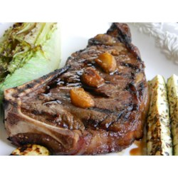 Garlic Steak with Garlic Recipe - Garlic is the star in this recipe for grilled New York strip steaks with olive oil-roasted garlic.