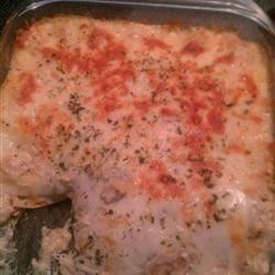Chicken Lasagna III Recipe - Cream of mushroom soup and cream of chicken soup meld with onions, cottage cheese, zingy sour cream, Parmesan, seasonings and chicken to make delicious layers for this delectable baked lasagna. Colby and mozzarella cheeses are tucked in for fun.