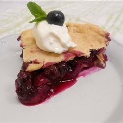 Three Berry Pie Recipe - Strawberries, raspberries, and blueberries are piled into a homemade pie shell, covered with a flaky top crust, and baked until bubbly and golden brown.