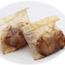 Asian Style Paper Wrapped Chicken Recipe - Chunks of boneless chicken breast are marinated in a sweet, savory Asian sauce with garlic and green onion. The chicken pieces are wrapped in foil triangles and deep-fried for a delicious appetizer that's fun to unwrap.