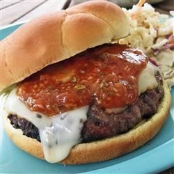 Horseradish Burgers Recipe - Grilled beef burgers are topped with distinctive Muenster cheese, and served with a zesty horseradish steak sauce mixture.