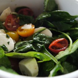 Spinach Caprese Salad Recipe - Drizzled with olive oil and balsamic vinegar, slices of tomato and fresh mozzarella lay on a bed of baby spinach in this greener version of a classic Caprese salad. Garnished with chopped fresh basil, the bright and simple flavors of summer are shown off in this colorful and elegant dish.