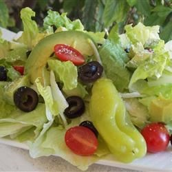 Karen's Spring Mix Salad Recipe - Baby salad greens tossed with avocado, tomato, olives and pepperoncini are coated in an herb vinaigrette and sprinkled with Parmesan.