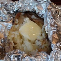 Campfire Baked Potatoes Recipe - Potatoes are coated with butter and wrapped in foil before being cooked in the hot embers of a camp fire.