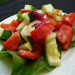 Tomato Cucumber Salad Recipe -  Diced tomatoes and cucumbers, chopped onion, and a splash of lemon juice. Chill and serve to four.