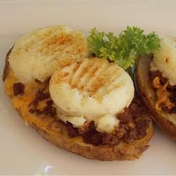 Chili Cheese Potato Skins Recipe - Fried potato skins are stuffed with a cheesy beef mixture and mashed potatoes, and seasoned with chili powder.