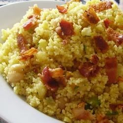 Curried Couscous Salad with Bacon Recipe - Couscous, garbanzo beans, caramelized onion, diced red bell pepper, carrot, and cucumber are tossed with a curried white balsamic vinaigrette, then sprinkled with crumbled bacon for a bold-flavored salad.