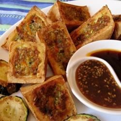 Thai Stuffed Tofu Recipe - A recipe for delicious stuffed tofu triangles filled with vegetarian stuffing turns this basic veggie staple into a fancy dish that is great for a light meal or as part of a sushi tray. Serve alongside cooked rice and drizzle the triangles with teriyaki sauce.