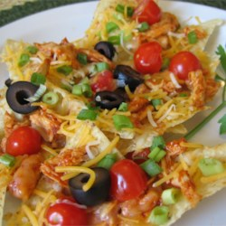 Restaurant Style Chicken Nachos Recipe - Tortilla chips are topped with a chicken and salsa mixture, melted cheese and tomato. These hearty nachos make a great snack and work well as a meal, too! Serve with sour cream and guacamole, if desired.