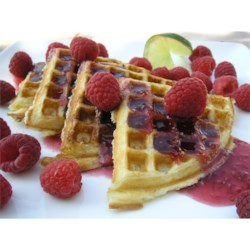 Eggnog-Raspberry Belgian Waffles Recipe - Eggnog added to waffle batter adds a touch of holiday flavor to these crisp Belgian waffles topped with warm raspberry preserves and fresh raspberries. Add a dollop of whipped cream if desired for a special Christmas breakfast or brunch.