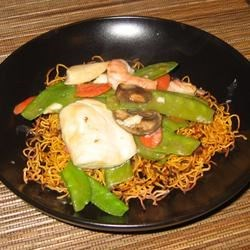 Chinese Noodle Pancakes with Asparagus Recipe - Chinese wheat noodles are double cooked, first in water until al dente and then mounded in a frying pan until crisp and brown. Then its smothered with a delicious sauce made from rice wine, soy sauce and wilted spinach. Next comes asparagus simmered in garlic and ginger.
