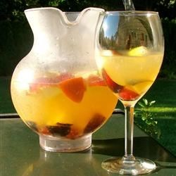 White Peachy Sangria Recipe - Sweet dessert wine teams up with peaches, strawberries, mango, and pineapple chunks for a light-colored sangria with a tropical taste. Make it the day before--it's great on a hot day.