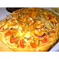 Garlic Chicken Pizza Recipe - A true gourmet pizza, made even better because it's fast, easy, and inexpensive! Grilled chicken, tomato wedges, red onions, and green peppers topping a garlic-parmesan sauce and mozzarella - it's the most beautiful pizza you'll ever see...or eat!