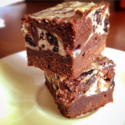 Chunky Cheesecake Brownies Recipe - This popular brownie has a creamy cheesecake layer sandwiched between fudgy chocolate layers made chunky with chocolate chips, then swirled with a knife for a marbleized top.
