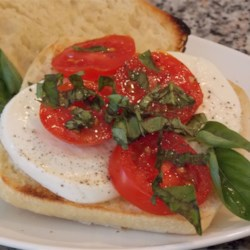 Caprese Salad Sandwiches Recipe - Red, ripe tomatoes, mozzarella cheese, and fresh basil leaves make a wonderful summer sandwich when combined with dark artisan bread and white truffle oil.