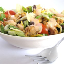 Grandma's Easy Turkey Taco Salad Recipe - Seasoned ground turkey is tossed with black beans, lettuce, tomato, tortilla chips, and dressing.