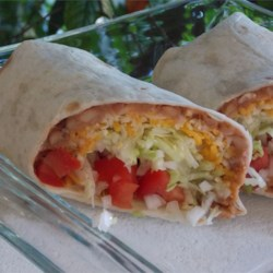Rick's Big Bad Bean Burrito Recipe - This hearty burrito is made with a whole-wheat tortilla wrapped around vegetarian refried beans, avocado slices, and pico de gallo for a filling lunch or dinner.