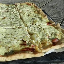 Sauerkraut on Bread Dough Recipe - A thin sheet of dough is sprinkled with bacon and sauerkraut, then drizzled with a spiced sour cream and baked until golden.  This goes really well with a crisp Riesling or German beer!