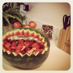 Watermelon Fruit Salad Bowl Recipe - Lightly sweetened melons, grapes and tropical fruits are served in a carved watermelon-rind 'bowl'. Try cutting a scalloped, or sawtooth, rim around the edge of the watermelon for a special presentation.