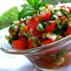 Middle Eastern Tomato Salad Recipe - A fresh summertime salad of garden cucumbers, tomatoes, and sweet onion is flavored generously with parsley and fresh mint. The dressing is just olive oil and lemon juice.