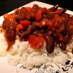 Spicy Crispy Beef Recipe - Deep fried strips of flank steak, sauteed with onion and red pepper in a spicy but sweet soy sauce. Serve with steamed rice and vegetables.