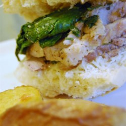 Philadelphia Style Roast Pork Sandwiches Recipe - Pork is roasted with garlic and herbs, then topped with savory cooked spinach and manchego or provolone cheese and piled into crusty sandwich rolls in this South Philly favorite.