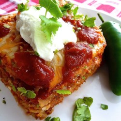 Mexican Lasagna Lite Recipe - Mexican-inspired light ingredients including refried beans, prepared enchilada sauce, sour cream, and ground turkey are layered like a lasagna and baked for a lower-fat version of the popular casserole.