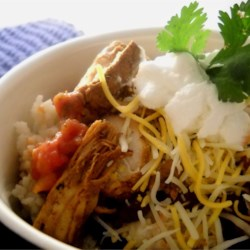 Fast Chicken Over Black Beans and Rice Recipe - Keep black beans, a couple of cooked chicken breasts, rice, and a few other ingredients on hand so you can make this quick Mexican-inspired chicken dish anytime. Use your choice of cheese.