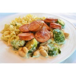 Kielbasa with Brussels Sprouts in Mustard Cream Sauce Recipe - The saltiness of the kielbasa combined with the bitter, gentle crunch of the Brussels sprouts and the mildness of the beans is well-balanced perfection.