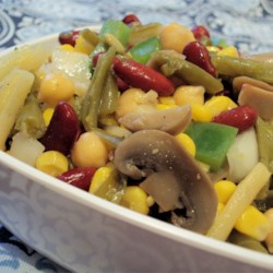 Three Bean Salad with Corn Recipe - Mix together a variety of canned vegetables and beans with a homemade vinaigrette dressing for an easy picnic salad.