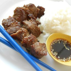 Beef Kushiyaki Recipe - Thinly-sliced pieces of steak are marinated in a savory-sweet mix of rice vinegar and soy, and rolled around pieces of green onion. Broiled on bamboo skewers, they make a tasty little appetizer bite.