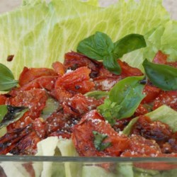 Roasted Tomato Salad Recipe - Roasted tomatoes with onion and herbs are served warm atop tender lettuce leaves with shaved Parmesan cheese in this terrific salad.