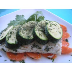 Halibut Wrapped in Dill Packages Recipe - Halibut fillets are flavored with lemon and dill and packaged with vegetables in parchment paper. They are quick to prepare and easy to clean up.