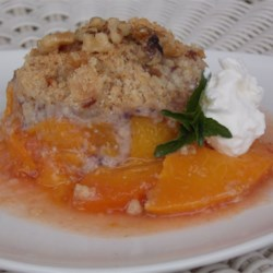 Peach Crisp with Oatmeal-Walnut Topping Recipe - Serve this tasty peach crisp slightly warm with a scoop of vanilla ice cream. The tender, buttery crisp topping contains walnuts and rolled oats.