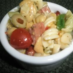 Conner's Birthday Pasta Salad Recipe - Tri-colored pasta is tossed with olives, kidney beans, garbanzo beans, Cheddar cheese, and Italian dressing for a light and easy side dish for parties or picnics.