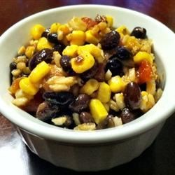Kelly's Black Bean Salad Recipe - This Mexican-inspired black bean salad combines rice, corn, and tomatoes with a spicy vinaigrette dressing. It will be loved by the whole family.