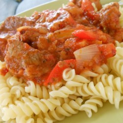 Swiss Steak Italian Style Recipe - Bite-sized pieces of round steak are sauteed with onions, then simmered with celery and green pepper in marinara sauce with red wine. Serve over egg noodles.