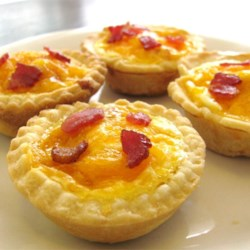 Bacon and Egg Breakfast Tarts Recipe - The perfect brunch treat, small pastry shells are made from prepared pie crust and filled with bacon or ham, shredded cheddar cheese, and egg. Then they are topped with a bit of milk, nutmeg and pepper. The tarts are baked until the eggs are soft cooked.