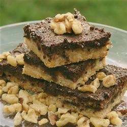 Chocolate Walnut Bars Recipe - A crunchy walnut crust is topped with rich chocolate batter and dusted with confectioners' sugar to make an elegantly festive dessert.