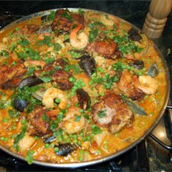 Easy Paella Recipe and Video - In this version of the classic Spanish dish, chicken, chorizo sausage, and shrimp combine with rice simmered in broth and flavored with saffron threads, garlic, onions, red pepper flakes, paprika, and bay leaf.