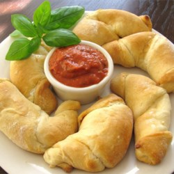 Pizza Moons Recipe - Classic pizza fillings are baked inside refrigerated crescent rolls for a fast and fun snack.