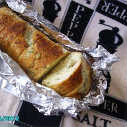 Easy Cheesy Garlic Bread Recipe - Butter, garlic powder, and Parmesan cheese make a terrific spread for French bread. You'll get plenty of oohs and ahs when you pull this out of the oven.
