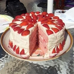 Strawberries and Cream Cake Recipe - This cake truly lives up to its name!  Three yellow cake layers are filled with strawberry-studded whipped cream, covered with a fluffy cream cheese frosting and topped with more strawberries.