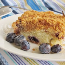 Sour Cream Blueberry Coffee Cake Recipe - Sugary crumbles and blueberries are baked between layers of fluffy sour cream coffee cake in a dessert your guests will love.