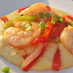 Garlic Cheese Grits with Shrimp Recipe - Grits are cooked with garlic flavored processed cheese, and served with sauteed shrimp and tomatoes.