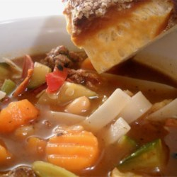 Sue's Minestrone Recipe - Browned ground turkey and crisp-cooked bacon are combined with Italian-style mixed vegetables, beef consomme, dried pasta,  and a can of bean and bacon soup in this dish seasoned with oregano and basil.
