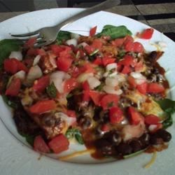 Mexican Chicken and Black Bean Salad Recipe - Chicken breast is baked in a tomato-based sauce and served atop a bed of spinach leaves in this simple salad. Black beans, cheese, sour cream, and salsa toppings provide a Mexican flair.