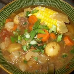 Caldo de Res (Mexican Beef Soup) Recipe - This is an extremely hearty and satisfying soup, made from scratch with beef bones, cabbage, potatoes, corn, chayote, and cilantro. Garnish with slivered raw onion, lime juice, jalapenos, and more cilantro.