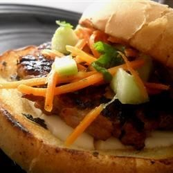 Banh Mi Burgers Recipe - A marinated cucumber and carrot pickle mix tops off grilled pork burgers that have been flavored with sesame oil and ginger. The cucumber pickle mix is made ahead of time and marinated for several hours. The burgers are served on sesame seed buns for a southeast Asia-inspired treat.