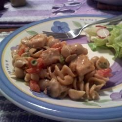 Mari's Chicken and Pasta Recipe - Savory chicken chunks with peas and tomato served over fettuccini pasta flavored with chicken and white wine broth.